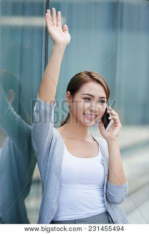 Cheerful Vietmnamese Business Woman Talkig On Phone And Rising Hand To Catch Taxi
