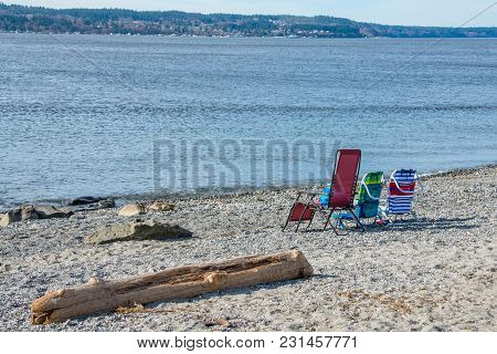 Three Empty Colorful Folding Beach Chairs Looking Out To Sea. Driftwood. Copy Space.