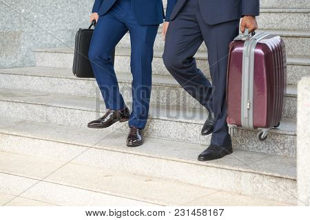 Business People With Baggage Going Down The Stairs