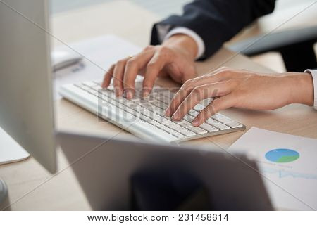Hands Of Businessman Typing On Keyboard At His Table