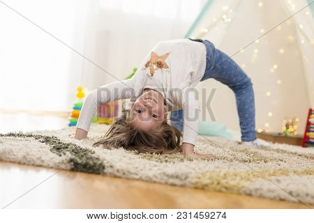 Cheerful Little Girl Doing Backbend, Playing In Her Playroom And Having Fun