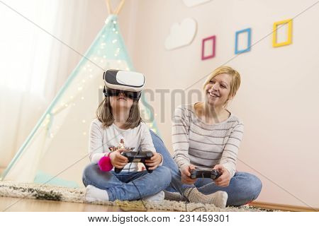 Mother And Daughter Sitting On The Floor In A Playroom, Playing 3d Vr Game And Having Fun. Focus On