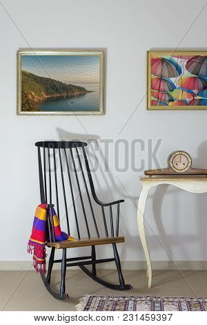 Interior Shot Of Vintage Rocking Chair And Antique Desktop Clock On Old Style Vintage Table On Backg