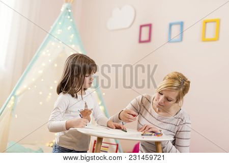 Mother And Daughter Playing In A Play Room, Drawing With Crayons. Focus On The Daughter