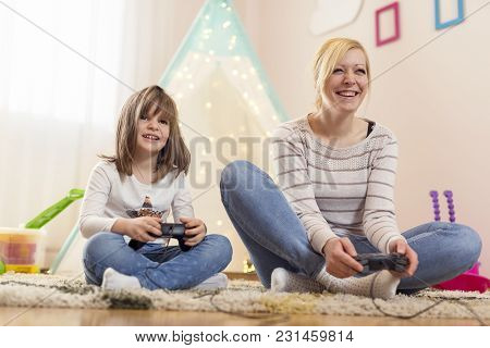 Mother And Daughter Sitting On The Floor In A Playroom, Playing Video Games And Having Fun