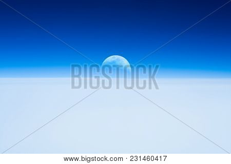 Half Moon Rising From The Earth Horizon Above The Clouds.