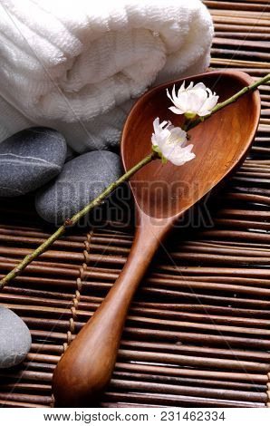 Peach flowers with spoon and gray stones, roller towel on mat background