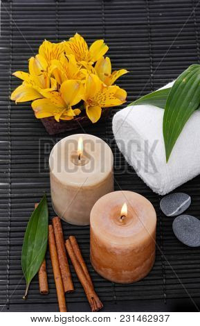 Spa setting with candle, towel ,orchid in bowl, cinnamon on mat