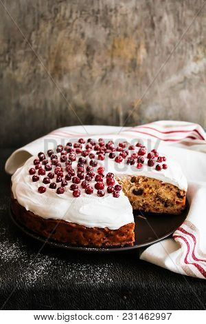 Cake With Dried Fruits And Nuts Decorated With Sweet Vanilla Meringue And Fresh Cranberry Dusted Wit