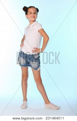 Happy Slender Cheerful Teenage Girl In Full Growth. The Child Gracefully Poses And Has Fun. The Youn