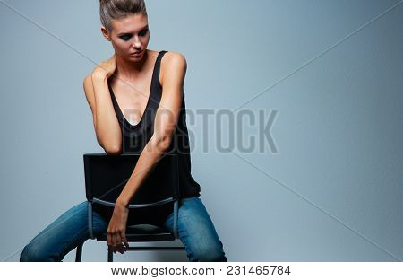 Beautiful Woman Sitting A Chair, Isolated On Gray Background .