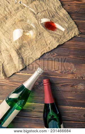 Image Of Two Wine Bottles And Wine Glasses On Napkin On Brown, Wooden Background.