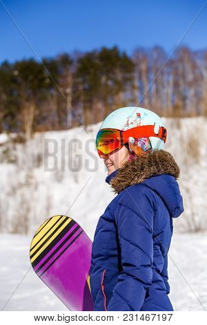 Side View Of Sporty Woman Wearing Helmet With Snowboard Looking At Camera On Winter Day