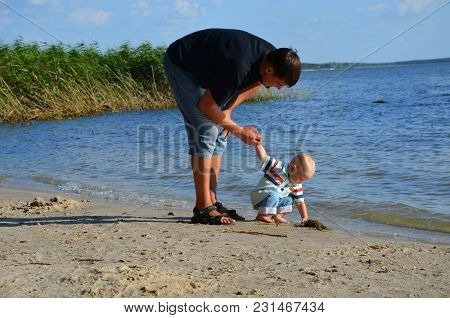 Man, Father, Playing With The Child, Supporting Him And Guarding, Near The River