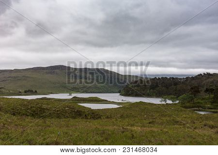 Kinlochewe, Scotland - June 10, 2012: Silver Colored Loch Clair Under Heavyt Gray Sky With Small Isl
