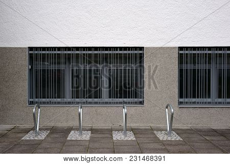 Modern And In Series Arranged Bicycle Racks Made Of Stainless Steel In Front Of Barred Windows.