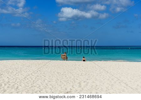 Oranjestad, Aruba - January 6, 2018: A Person Tans On A Sunbed On The Shore Of The Caribbean Sea Of