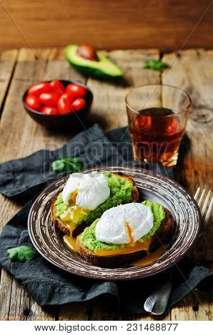 Poached Egg Avocado Rye Toasts On A Wood Background