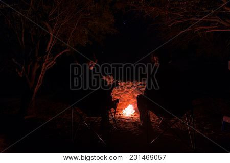 Couple Sitting At Burning Camp Fire In The Night. Camping In The Forest Under Starry Sky, Namibia, A