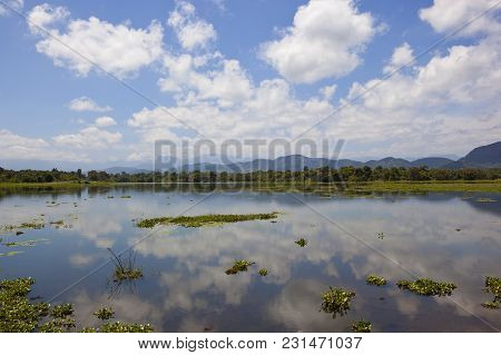 Beautiful Mirror Lake With Woodland And Mountains In Wasgamuwa National Park Under A Blue Sky With F