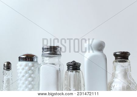 A Row Of Salt Shakers Frame White Copy Space.