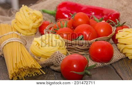 Long And Twisted Pasta With Cherry Tomatoes On A Brown Wooden Table On A Beige Bag