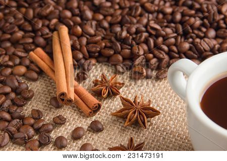 Roasted Coffee Beans Are Scattered On Beige Burlap With Cinnamon Sticks And Anise On The Right In Th