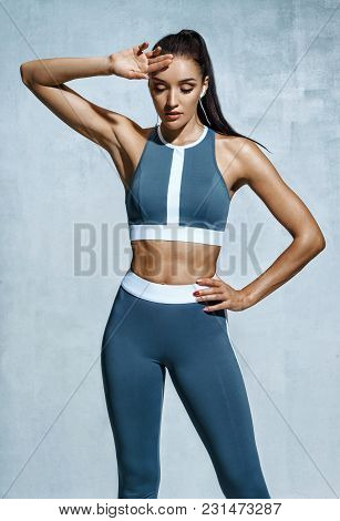 Tired Woman Resting After Doing Sports. Photo Of Latin Woman In Fashionable Sportswear On Grey Backg