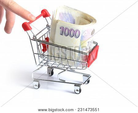 Finger Pushing A Red Shopping Cart With Czech Banknotes Inside Isolated On White Background