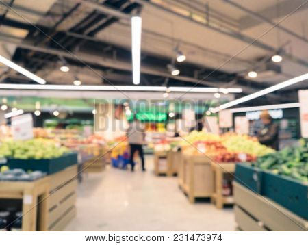 Abstract Blurred Supermarket Aisle With Fruits And Vegetables On Shelves And Unrecognizable Customer