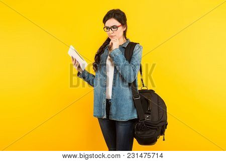 Portrait Of Attractive Young Woman In Denim Jacket And Eyeglasses Holding Travel Bag And Tablet Pc I