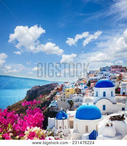 Oia, Traditional Greek Village Of Santorini With Blue Domes Of Churches Under Sky With Flowers, Gree