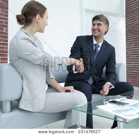 Business people shake hands while sitting in the workplace