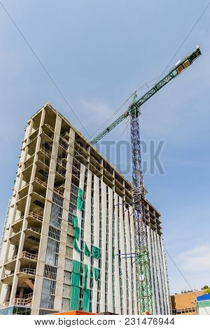 New Building, Construction Of A Modern Multi-storey Building With A Tower Crane And Other Constructi