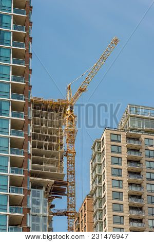New Building, The  And Other Construction Equipment In The City, Against A Background Of Blue Sky An