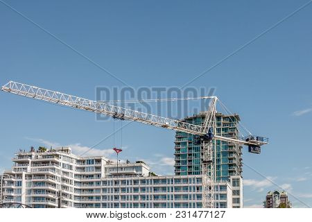 Crane Builds Modern High-rise Buildings And Buildings On A Summer Day Against A Blue Sky And White C