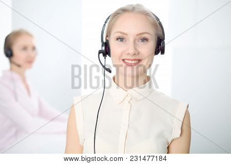 Image Of Bright Call Center. Focus On Young Blonde Woman In A Headset.