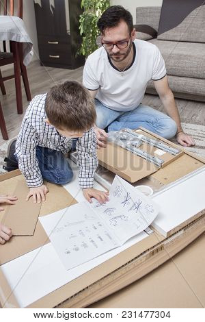 Father And Son Kneel On The Carpet In Front Of The Box With Elements For Self-assembly And Read The