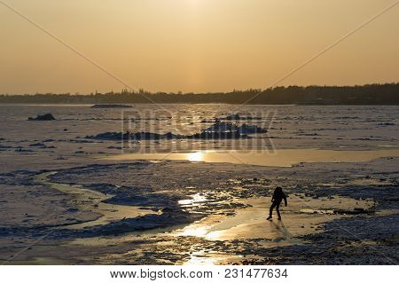 Man Tries To Pass On The Thin Ice Of A Frozen Sea On A Winter Evening