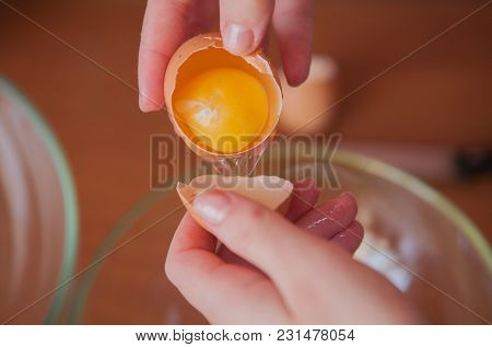 A Woman Holding An Open Chicken Egg In Her Hands.
