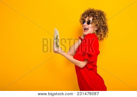 Portrait Of A White Happy Woman With Afrro Hairstyle In Red Dress And Sunglasses Holding Fan Of Euro