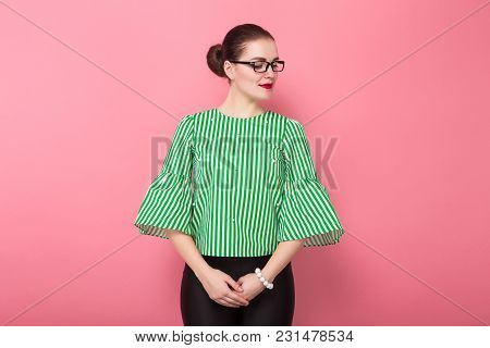 Portrait Of Attractive Businesswoman With Hair Bun In Striped Blouse And Eyeglasses Standing Straigh