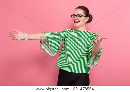 Portrait Of Attractive Businesswoman With Hair Bun In Striped Blouse And Eyeglasses Holding Arms Spr