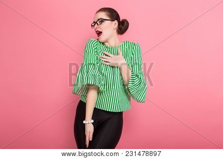 Portrait Of Attractive Businesswoman With Hair Bun In Striped Blouse And Eyeglasses Posing With Palm
