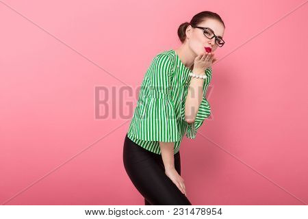 Portrait Of Attractive Businesswoman With Hair Bun In Striped Blouse And Eyeglasses Blowing Air Kiss