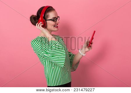 Portrait Of Businesswoman With Hair Bun In Striped Blouse And Eyeglasses Listens To Music In Headpho
