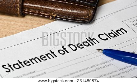Statement Of Death Claim Form On A Wooden Surface. Next Is A Blue Fountain Pen, Leather Purse