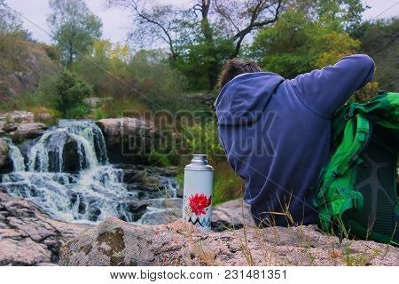 Unrecognizable Traveler Searching Tea Cup From Thermos On The Rocks At Waterfall Background. Theme T
