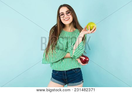 Portrait Of Attractive Young Long-haired Girl In Striped Shirt, Glasses And Jeans Shorts Holding Red