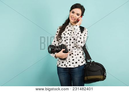 Portrait Of Young Attractive Woman Photographer In White Shirt Holding Camera And Bag Talking On Tel